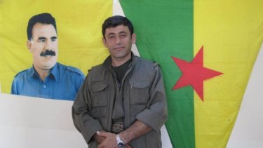 Commander Badr Khan standing under a flag featuring the image of Abdullah Ocalan, the imprisoned PKK leader.