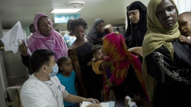 A Chinese doctor interviews Kenyans waiting to receive free  medical attention.