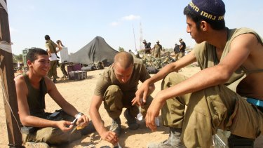 Israeli soldiers from an infantry unit prepare food at an Israeli village on the border with Gaza on Sunday.