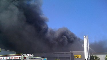 Plumes of black smoke rise into the air over the factory.