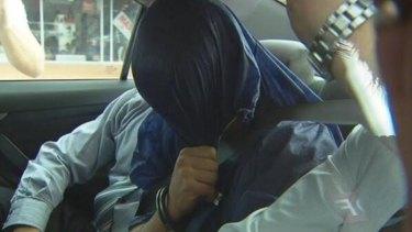 The suspect leaves Coffs Harbour with Brisbane detectives on Tuesday.