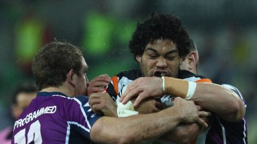 Former Storm man Adam Blair of the Tigers is tackled.