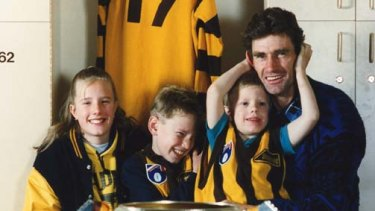 Hawthorn legend Michael Tuck with his children, Renee, Shane and Travis, on his knee, in 1991.