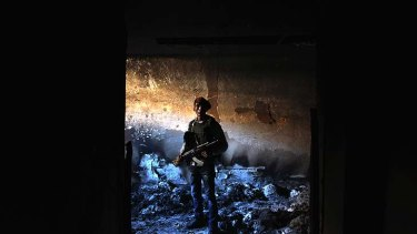 A rebel militiaman stands in the ashes of an alleged torture chamber of the former Libyan Internal Security force in Benghazi on Monday.