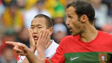 North Korea's striker Jong Tae-Se reacts next to Portugal's defender Ricardo Carvalho.