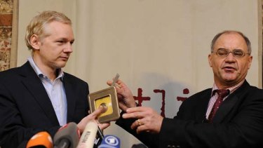 WikiLeaks founder Julian Assange, left, receives CDs from former banker Rudolf Elmer.