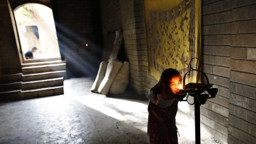 A displaced Yazidi girl worships at   Lalish temple in Shikhan last year.