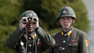 A North Korean soldier looks at the southern side through binoculars.