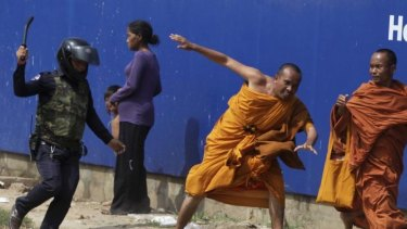 A security guard chases away Buddhist monks from a camp occupied by anti-government demonstrators in Phnom Penh.