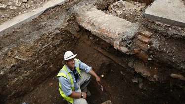 Buried treasure? ... Archaeologist Mathew Morris sits in the trench where the skeleton remains were found.