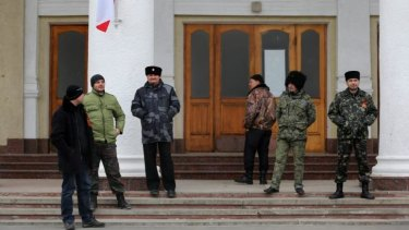 "Pro-Russian ""self-defence"" forces and Cossacks  in front of a building that joins the control tower at Simferopol airport."