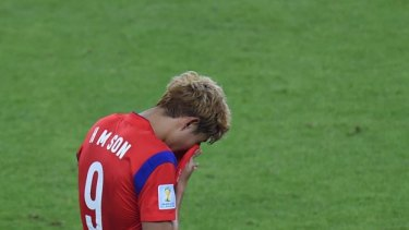 South Korea's midfielder Son Heung-Min reacts at the end of the Group H football match between South Korea and Algeria.