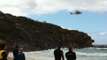 A rescue helicopter hovers over the area where the plane went down at North Curl Curl.