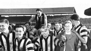 Collingwood players carry acting captain Murray Weideman off the field after he was instrumental in the Magpies scoring an upset win over Meelbourne in the 1958 grand final.