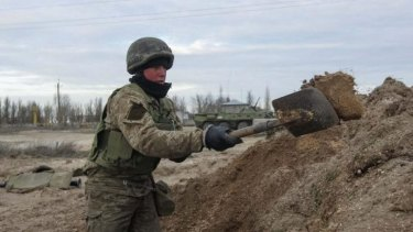 A Ukrainian serviceman digs a trench at a checkpoint near the village of Strelkovo in Kherson region adjacent to Crimea.