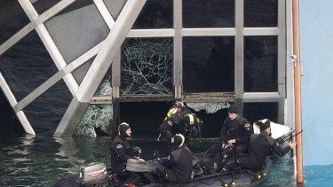 Marina Militare scuba divers prepare to enter a broken window of the Costa Concordia.