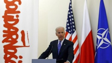 US Vice-President Joe Biden addresses the media in Poland, with US, Polish and NATO flags behind him, as well as a banner from the Solidarity movement which weakened Soviet control over Poland in the 1980s.