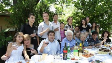Wine dynasty ... extortion victim John Casella, centre left, and his father, Filippo, at a family gathering near Griffith. Their business produces Yellow Tail wine.