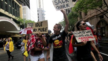 Alicia Mellor, 20, Davey Thompson, 21, and Kaylah Tyson, 25, march through the streets of Brisbane as part of the Invasion Day protest on Australia Day.