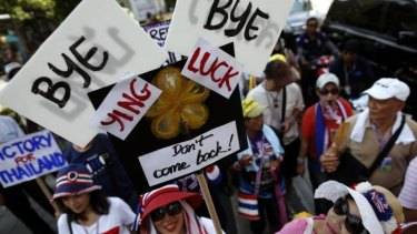 Anti-government protesters carry signs against ousted Prime Minister Yingluck Shinawatra as they march in central Bangkok.