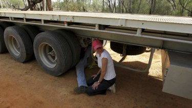Protest: Coonamble farmer Ted Borowski locks himself onto the axle of a heavy articulated vehicle, bringing a Santos convoy to a standstill in the Pilliga State Forest.