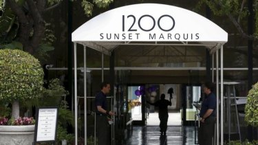 A man carries flowers into the Sunset Marquis hotel where U2 tour manager Dennis Sheehan was pronounced dead in his hotel room, according to local media, in West Hollywood.