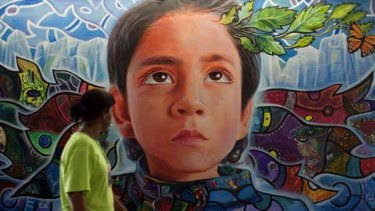 A woman walks past a mural in the climate village during the United Nations Framework Convention on Climate Change, in the Mexican seaside resort of Cancun.