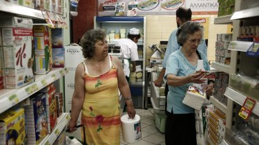 Facing long lines ... Customers shop for food products at a local supermarket in Athens, Greece.