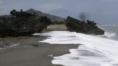 US Navy amphibious assault vehicles roll into the water facing the South China Sea in a joint naval exercise with the Phillipines on Monday, June 30.