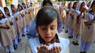 Living in hope ... Pakistani schoolgirls pray for peace campaigner Malala Yousafzai.