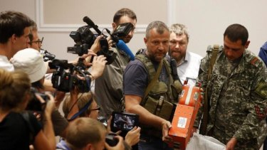 A pro-Russian separatist shows members of the media a black box belonging to Malaysia Airlines flight MH17, before its handover to Malaysian representatives, on Tuesday.