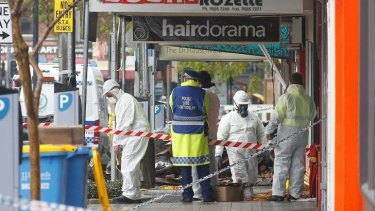 Asbestos removalists work on Saturday at the scene of the explosion.