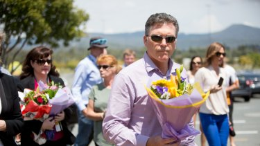 Dreamworld chief executive Craig Davidson leaves flowers at the site on Friday after a private memorial service at Dreamworld.