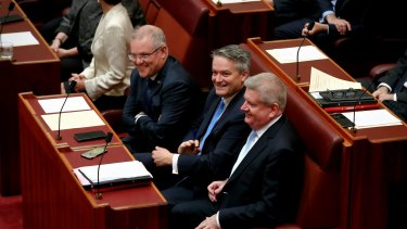 NBN Shareholder ministers Senator Mathias Corman (centre) and Senator Mitch Fifield (right), sitting with Treasurer Scott Morrison at the opening of Parliament in April.