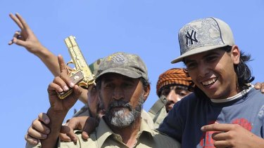 Libyan National Transitional Council fighters hold what they claim to be the gold-plated gun of the late Libyan leader.
