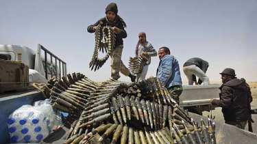 Libyan rebel fighters load a truck with ammunition on the outskirts of Ajdabiya.