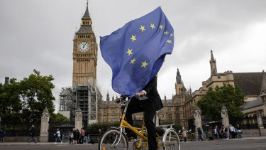 """An anti-Brexit demonstrator cycles outside the Houses of Parliament in London. """"We are looking at Brexit with interest but not fear,"""" says Macquarie Group chief executive Nic Moore."""