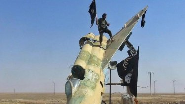 Flag waving: Islamic State fighters waving the group's flag from a damaged display of a government fighter jet following the battle for the Tabqa air base, in Raqqa, Syria.