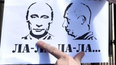 A protester sticks a sign bearing a portrait of Russian President Vladimir Putin and a derogatory term during a rally against the Russian president in front of the Russian embassy in Kiev.