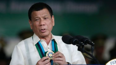 Philippine President Rodrigo Duterte shows a medal during his speech to troops in Quezon City in December.