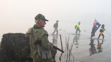 Protesters wade through the swamp at Dowds Morass, near Sale, as duck hunter Geoff Fisher looks on.