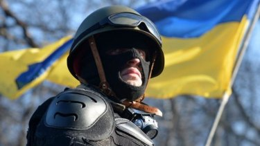 An anti-government opposition activist guards a barricade of the opposition in Kiev.