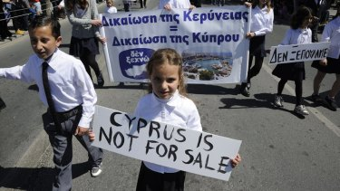 "Students hold placards, including one that reads in Greek ""we don't sell out ""during a parade for Greek independence day at the southern port city of Limassol, Cyprus."