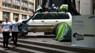 A muddied up 4WD with a sign that appears to mock Apple Maps at Australia Square in Sydney.
