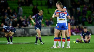 All over: Newcastle players celebrate their upset victory over Melbourne Storm at AAMI Park on Saturday night.
