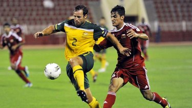 Lucas Neill moves the ball upfield for the Socceroos.