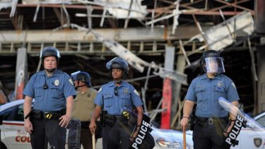Police wearing riot gear stage outside the remains of a burned convenience store on Monday in Ferguson, St Louis.