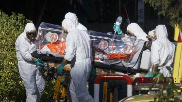Health workers transfer Ebola patient Father Miguel Pajares to a hospital in Madrid after flying him back from Liberia. A nurse has contracted the virus after treating the priest, who has since died.