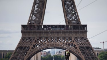 A man rides an 800-metre zip line from the second floor of the Eiffel Tower in Paris.