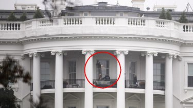 Law enforcement officers examine a window of the White House that was hit by a bullet.